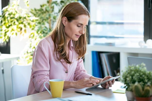オフィスでデジタルタブレットを使用して作業している自信を持って成熟したビジネス女性のショット。