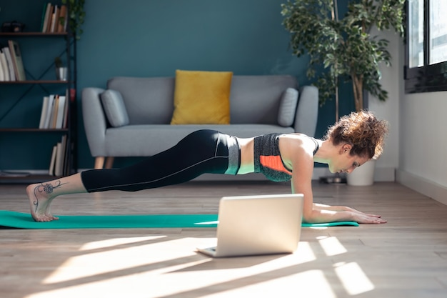 집에 있는 거실 바닥에 있는 노트북을 통해 온라인 체육관 수업을 마친 자신감 넘치는 젊은 여성의 사진.