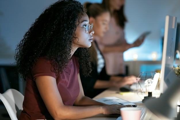オフィスに座ってラップトップで作業している自信を持って若いビジネス女性のショット。