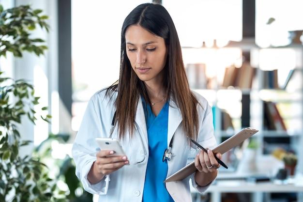클립보드를 들고 상담실에 서 있는 동안 휴대전화를 사용하는 자신감 있는 젊은 여성 의사의 사진.
