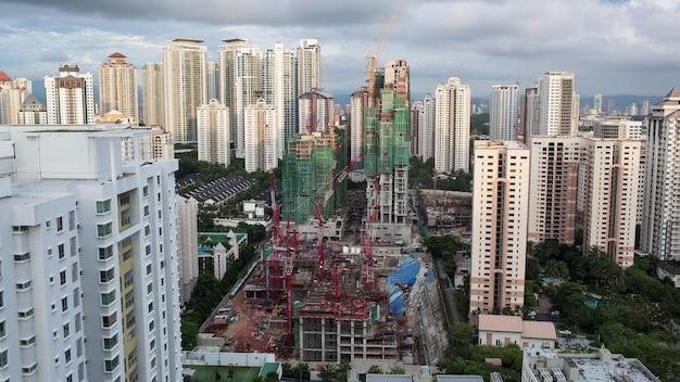Снимок строительных работ в жилом районе куала-лумпура с многоэтажными домами. облака плывут над городом и наступает ночь.