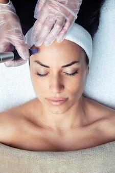 스파 센터에서 회춘을 위해 얼굴에 더마펜으로 메조테라피 주사를 만드는 미용사 사진.