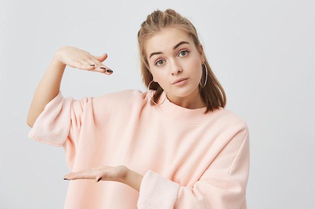Выстрел из милой очаровательной девушки в стильной розовой толстовке с длинными рукавами, показывая что-то размером с руки, активно жестикулируя. блондинка европейская женщина позирует.