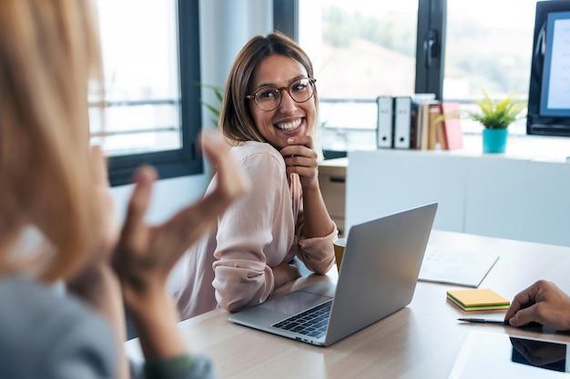 Снимок милой молодой женщины, слушая своего коллегу и улыбаясь во время работы с компьютером в коворкинге.