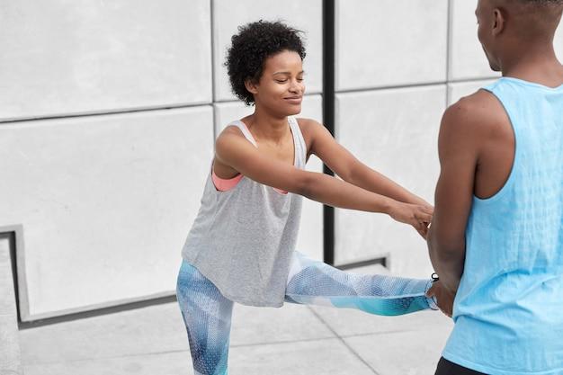 肌の色が濃いヒップスターの女の子のショットは、持久力が高く、ストレッチ運動をするのに役立つ男の手で脚を上げ、カジュアルなスポーツ服を着て、外でポーズをとります。エクササイズ、アシスタンス、フィットネスのコンセプト
