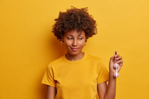 어두운 피부를 가진 여성의 샷은 내부 쾌락을 위해 새로운 섹스 토이 컬렉션에서 쉽게 제거 할 수 있도록 신축성있는 끈으로 완성 된 질 공을 보여 주며, 추가적인 감각을 위해 성감대에 삽입합니다.