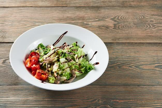トマトと木製のテーブルcopyspace珍味おいしい食欲飢餓メニューレストランカフェランチランチディナーコンセプトのソースで飾られたチキンのおいしいサラダのショット。