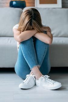 집 거실 바닥에 앉아 있는 동안 우울한 젊은 여성이 자신의 문제에 대해 생각하는 사진.