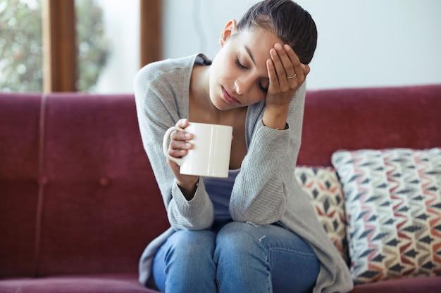 집에서 소파에서 커피를 마시는 동안 두통이 있는 우울한 젊은 여성의 총.