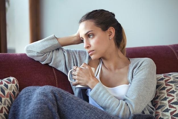 집에서 소파에서 커피를 마시는 동안 우울한 젊은 여성이 자신의 문제에 대해 생각하는 사진.