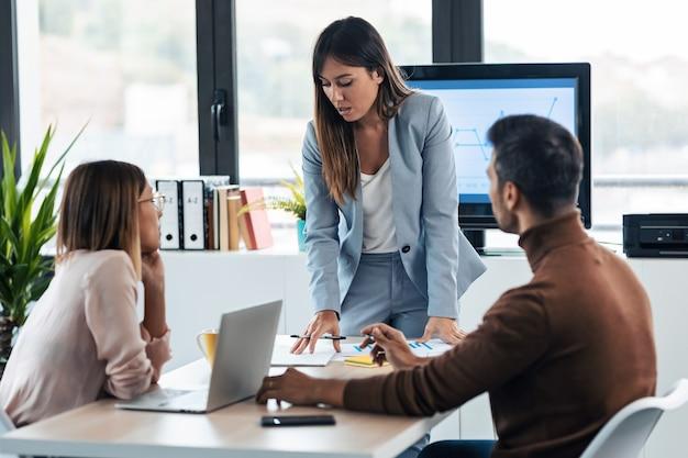 Снимок элегантной умной бизнес-леди, объясняющей проект своим коллегам со статистикой на компьютере в коворкинге.