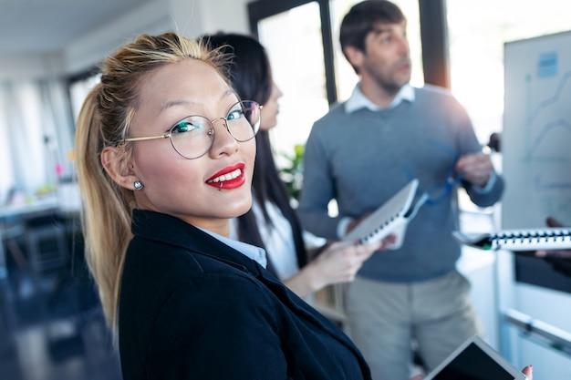동료들이 공동 작업 공간에서 프로젝트에 대해 설명하는 동안 우아한 젊은 여성 사업가가 카메라를 쳐다보는 사진.