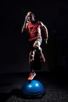 暗いスタジオで体操の半球ボスボールで運動を行うフィットアスリートのショット。
