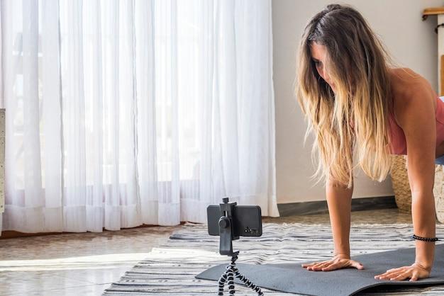 Выстрел фитнес-женщины, делающей упражнения на планке на коврике для йоги и с помощью мобильного телефона подходящая молодая женщина