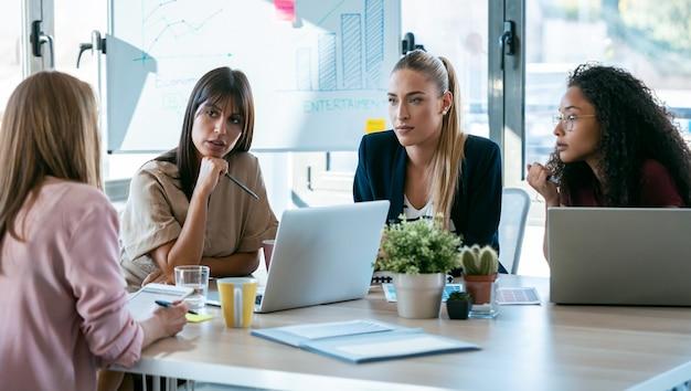 4人の美しいスマートビジネス女性のショットは、オフィスのコワーキングスペースの机の上でラップトップを使用して作業します。