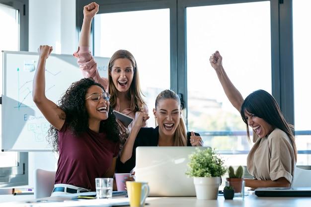 オフィスのコワーキングスペースでの勝利を祝いながら、4人の幸せなスマートビジネス女性が机の上でラップトップを使って作業するショット。