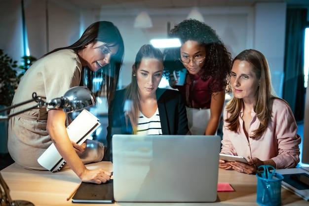 共同ワークスペースでコンピューター上で行われた最新の作業について話し、レビューしている4人の賢いビジネスウーマンのショット。