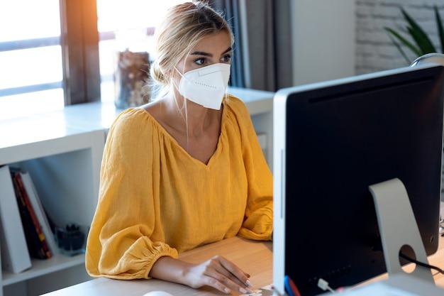 소규모 창업 고객에게 온라인으로 주문한 제품을 배달하기 위해 컴퓨터로 제품 주문을 확인하는 위생적인 안면 마스크를 쓴 프리랜서 여성 판매자의 사진.