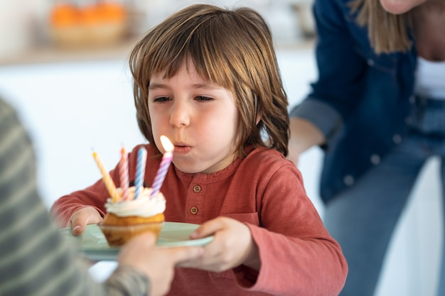 집에서 그의 생일 케이크에 촛불을 불고 재미있는 소년의 총.