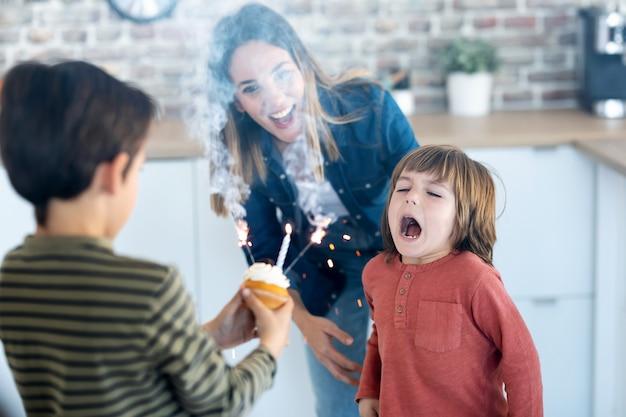 그의 동생이 집에서 그것을 들고 있는 동안 그의 생일 케이크에 촛불을 불고 재미있는 소년의 총. 프리미엄 사진