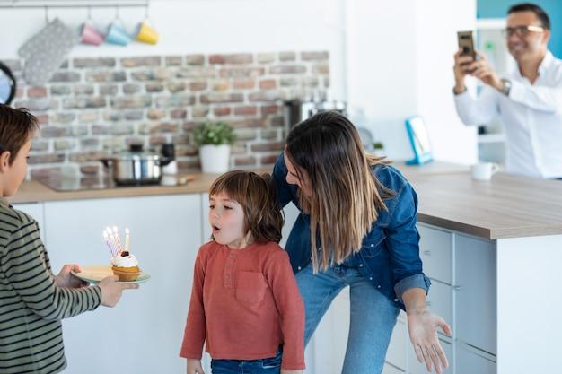 그의 동생이 집에서 그것을 들고 있는 동안 그의 생일 케이크에 촛불을 불고 재미있는 소년의 총.