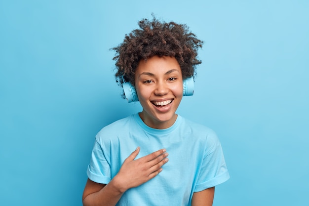 カジュアルなtシャツを着て前向きに着飾った嬉しいアフリカ系アメリカ人の女の子の笑顔のショットは、青い壁に対して面白がってポーズをとっているヘッドフォンを介して音楽を一覧表示します。モノクロームショット。ポジティブな感情。
