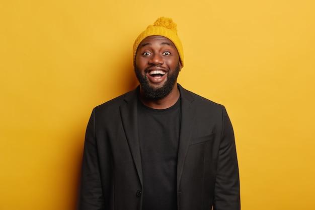 На снимке: довольный пухлый темнокожий мужчина позитивно смеется, радостно улыбается, носит черную элегантную одежду и яркий головной убор, стоит на желтом фоне, чувствует счастье.
