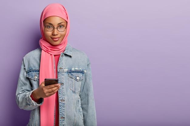 매력적인 표정으로 잘 생긴 어두운 피부의 여성의 샷은 분홍색 히잡과 데님 코트를 입고, 현대 휴대 전화를 들고, 중요한 전화를 기다리고, 빈 공간이있는 보라색 벽 위에 서 있습니다.