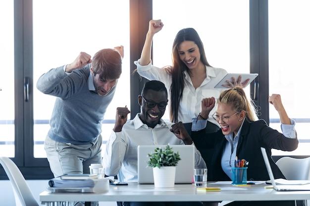 コワーキングスペースでラップトップを見ながら何かを祝う成功した若いビジネスマンのグループのショット。