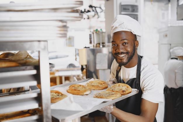 제조 제빵에서 스탠드에 신선한 빵의 트레이를 넣어 잘 생긴 베이커의 총. 아프리카 계 미국인.
