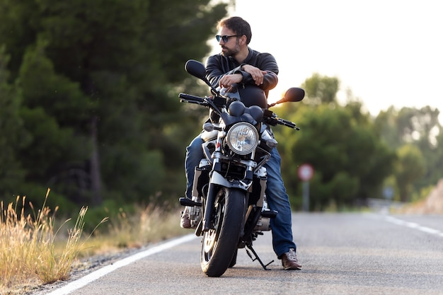 Снимок красивого бородатого байкера, смотрящего в сторону, сидя на своем мотоцикле и держа шлем.