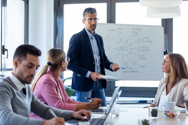 コワーキングプレイスで同僚にプロジェクトを説明するハンサムなビジネスマンのショット。