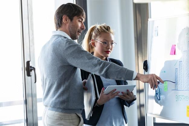 コワーキング場所で彼の同僚にプロジェクトを説明しながらホワイトボードを指しているハンサムなビジネスマンのショット。