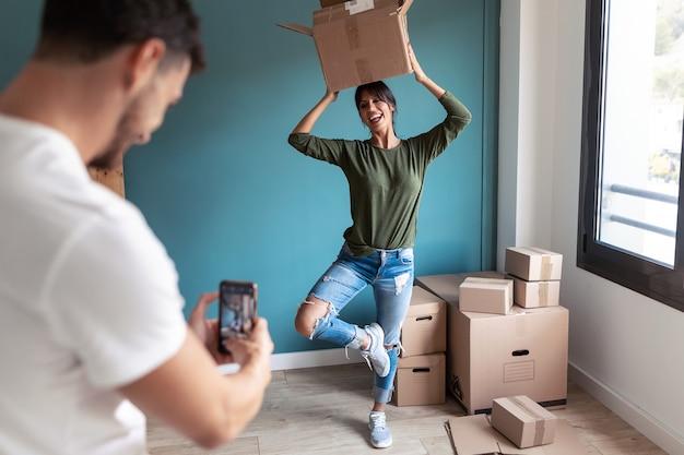 그녀가 새 집에서 움직이는 판지 상자와 농담하는 동안 스마트 폰으로 그의 재미있는 아내에게 사진을 찍는 잘 생긴 남자의 샷.