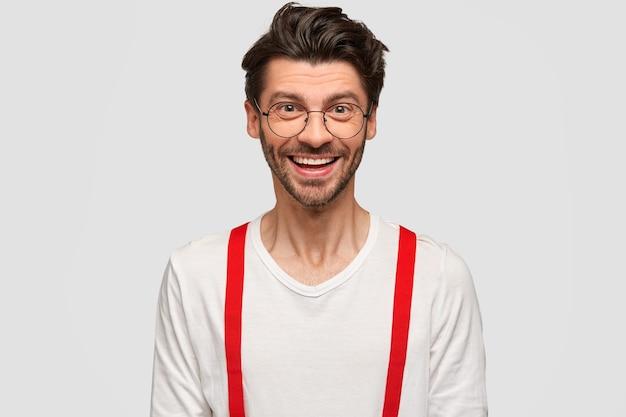 白い壁に隔離された、赤いブレース付きの白いシャツを着た、ポジティブな表情のハンサムな無精ひげを生やした男性のショット。眼鏡の陽気な男のフリーランサーは彼のキャリアの成功を喜ぶ