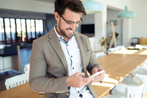 オフィスのテーブルに座っているときに彼のスマートフォンを使用してハンサムな若いビジネスマンのショット。