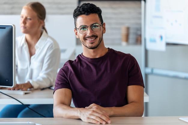 オフィスでコンピューターを使用しながらカメラを見ているハンサムな若い起業家のショット。