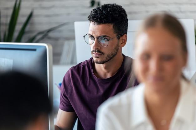 彼の同僚がオフィスで一緒に働いている間、コンピューターを使用しているハンサムな若い起業家のショット。