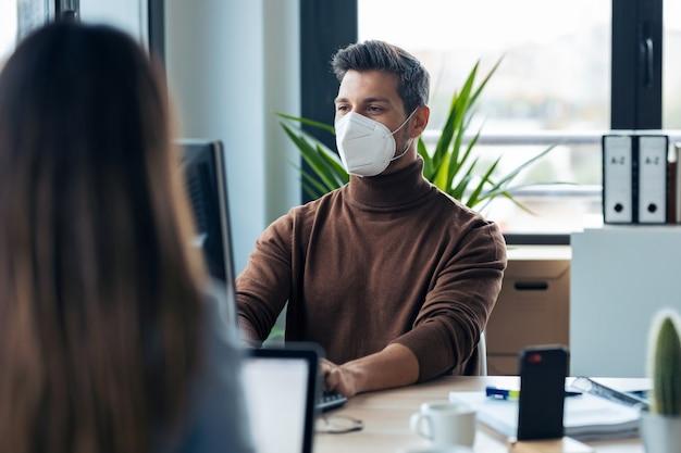 現代のスタートアップオフィスでコンピューターを使用して作業している衛生的なフェイスマスクを身に着けているハンサムな若い起業家のショット。