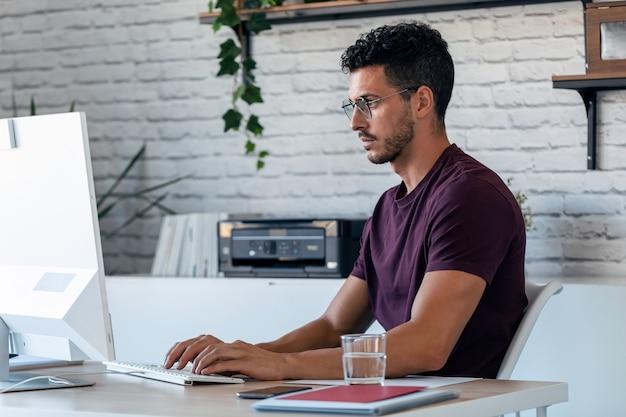 オフィスでコンピューターを操作しているハンサムな若い起業家のショット。