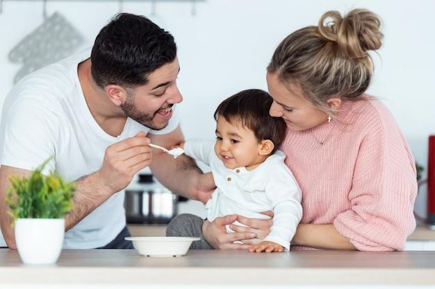Снимок красивого молодого отца, кормящего своего маленького сына, в то время как мать смотрит на них на кухне дома.