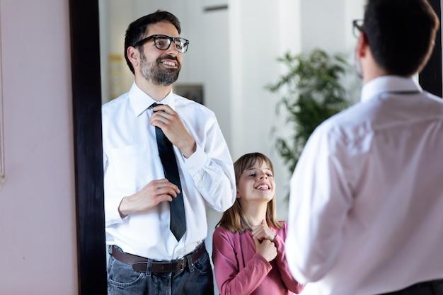 거울 앞에서 넥타이를 매는 잘생긴 젊은 아버지와 집에서 그것을 복사하는 예쁜 딸의 사진.