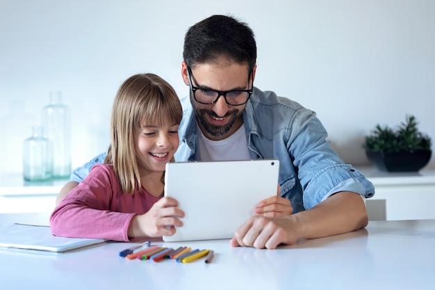 Выстрел красивый молодой отец с его маленькой дочерью с помощью цифрового планшета дома.