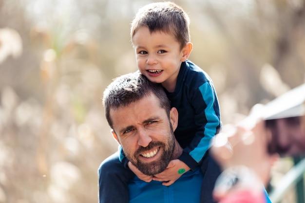 彼らが屋外で写真を撮っている間、カメラを見ている彼の幼い息子を肩に乗せたハンサムな若い父親のショット。