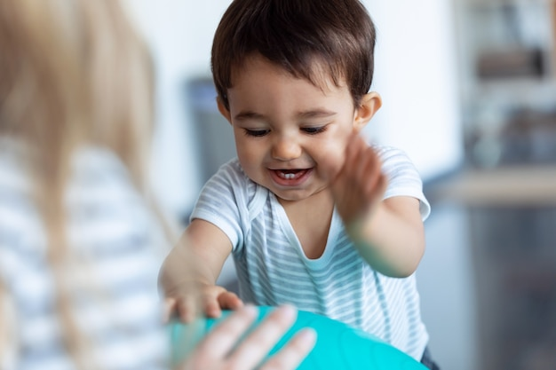 집에서 파란 공을 가지고 놀면서 웃고 있는 행복한 아기의 사진.