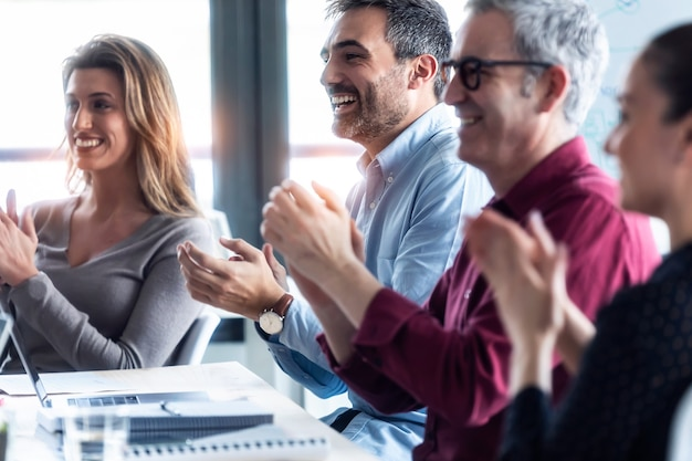 공동 작업 공간에 앉아 회의를 듣고 행복한 비즈니스 팀이 박수를 치는 장면.