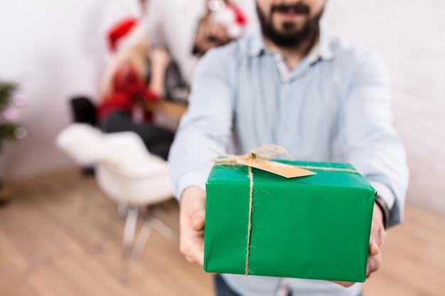 Выстрел счастливых друзей, наслаждающихся праздниками, фокусируется на подарке в руках человека на переднем плане