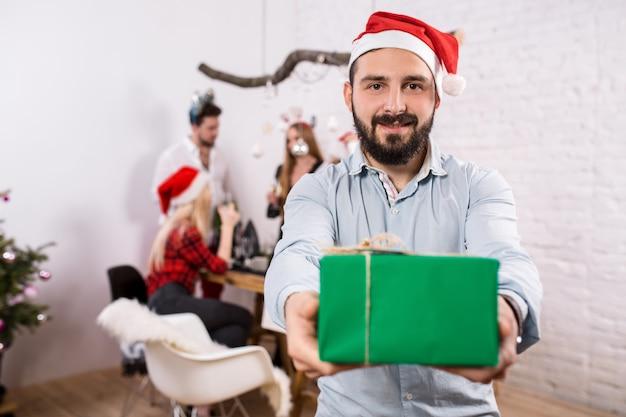 Снимок счастливых друзей, наслаждающихся праздником, сосредоточен на мужчине на переднем плане в красной рождественской шляпе