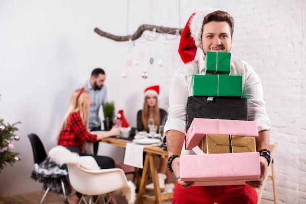 Снимок счастливых друзей, наслаждающихся праздником, фокусируется на мужчине с подарочными коробками на переднем плане в ...