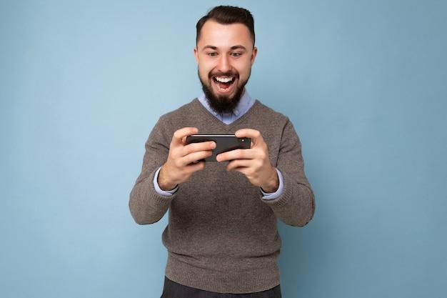 毎日の灰色のセーターを着ているひげを持つ幸せで楽しいハンサムな若いブルネットの無精ひげを生やした男のショット